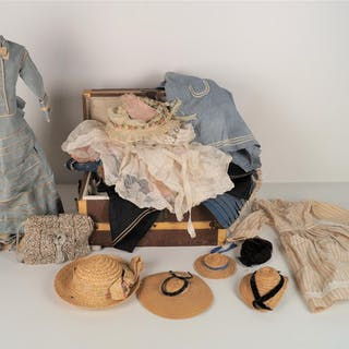 Petite malle bombée comprenant des éléments de trousseau dont robes et chapeaux