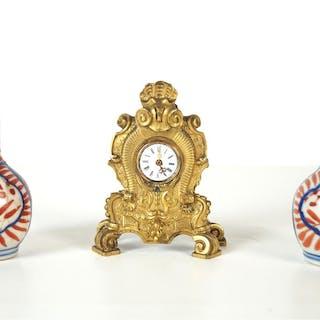 Garniture miniature comprenant une horloge en bronze doré de style rocaille